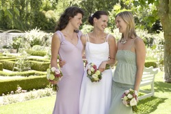 Cheerful bride with female friends holding bouquets in formal garden