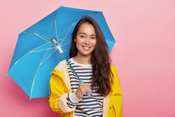 Cheerful brunette Asain woman with long dark hair, wears striped jumper, yellow raincoat, holds blue umbrella, has stroll during rainy day, isolated on pink. Bad weather doesnt spoil my mood