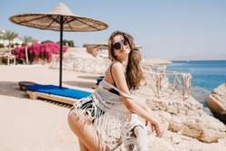 Cheerful brunette girl in sunglasses enjoying vacation, posing near the sea in summer morning. Beautiful young woman with long hair having fun on the beach, sunbathing with lovely face expression