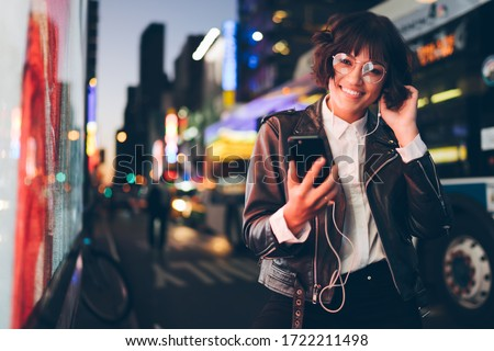 Cheerful brunette hipster girl in stylish eyewear and modern earphones listening and choosing audio songs on music app download on smartphone standing on metropolitan street enjoying night city