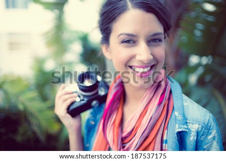 Cheerful brunette photographer standing outside smiling at camera on a sunny day