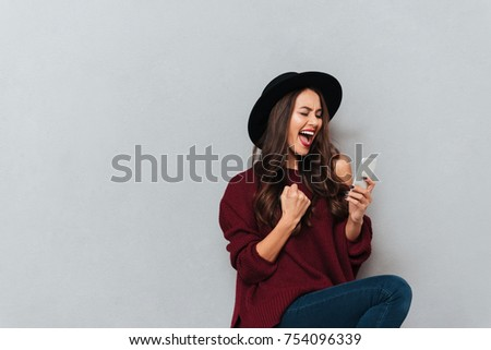 Cheerful brunette woman in sweater and hat using smartphone and rejoice over gray background #754096339
