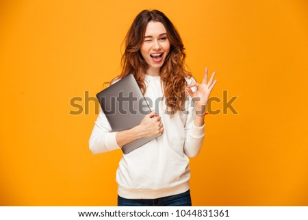 Cheerful brunette woman in sweater holding laptop computer and showing ok sign while winks and looking at the camera over yellow background