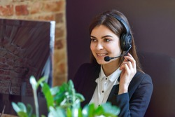 Cheerful brunette woman, kindly callcenter operator, wear black jacket and headphone set, sitting near computer pc before bricks wall loft background