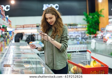 Cheerful brunette woman photographing product in supermarket