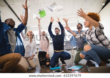 Cheerful business colleagues tossing papers at creative office
