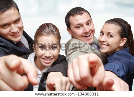 Cheerful business group of executives all pointing at you