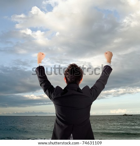 Cheerful business man standing in outside of ocean and rising hands.