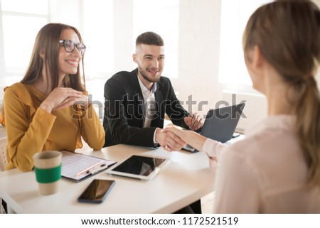 Cheerful business man with laptop and business woman in eyeglasses happily talking with applicant about work. Young employers spending job interview in modern office #1172521519
