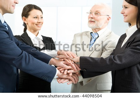 Cheerful business people joining their hands