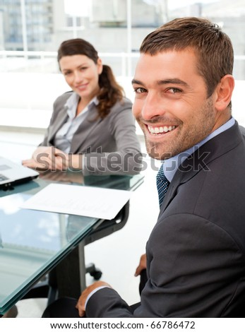 Cheerful business people sitting at a table with a laptop during a meeting - stock photo