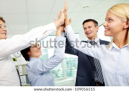 Cheerful business team holding their hands together with enthusiasm
