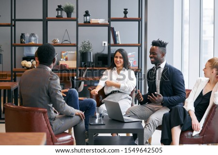 Cheerful business team sitting together on able discussing, smiling, break time, free time while working. Business meeting in office, african and caucasian partnership