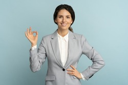 Cheerful business woman wear blazer in good mood smiling broadly, showing ok sign over studio blue color background. Positive office employee female advertises a product. Customer, sale, discount.