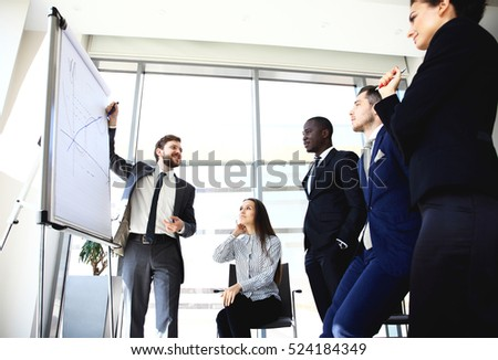 Cheerful businessman discussing a new business project with the members of his team #524184349
