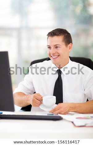 cheerful businessman drinking coffee while working on his computer in office