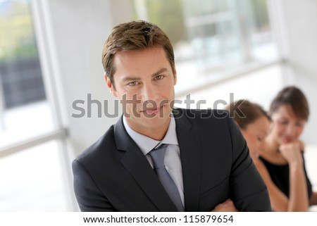 Cheerful businessman sitting in front of colleagues