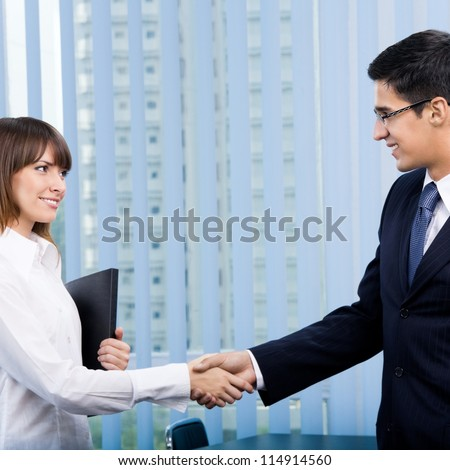 Cheerful businesspeople, or business person and client, handshaking