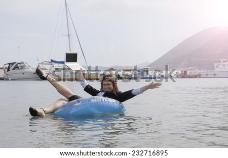 Cheerful businesswoman floating in ocean- business success