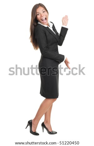 Cheerful businesswoman in black skirt suit presenting and showing copy space. Happy smiling full body portrait of a beautiful Asian / Caucasian young business woman model cut out on white background.