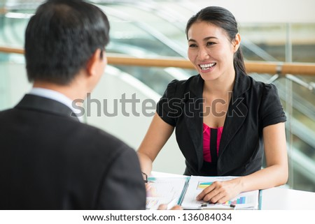Cheerful businesswoman providing a male entrepreneur with consulting services