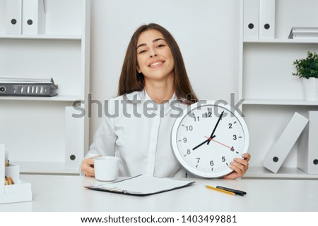 Cheerful Businesswoman with a clock in the hands of a desktop office finance office manager career #1403499881
