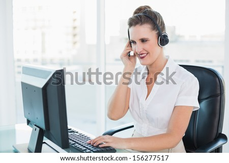 Cheerful call center agent working on computer while having a call in bright office