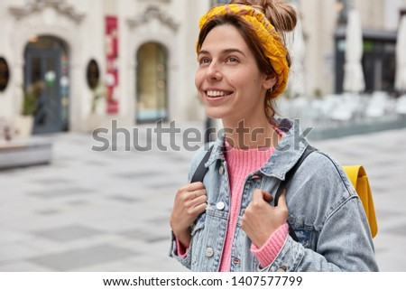 Cheerful carefree woman dressed in fashionable outfit, has charming smile on face, enjoys recreation time, carries small rucksack, strolls across city, being in good mood. Vacation, traveling #1407577799