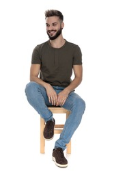 Cheerful casual man laughing while sitting on a chair on white studio background