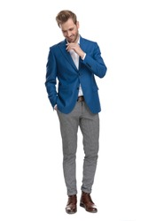 Cheerful casual men laughing and holding his hand in his pocket while looking down and wearing a suit, standing on white studio background
