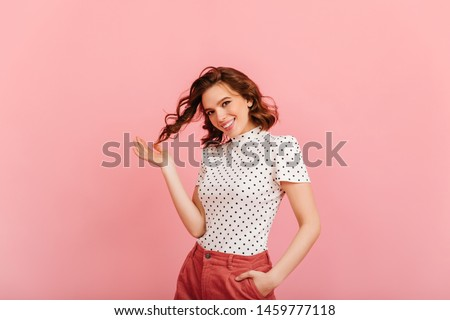 Cheerful caucasian girl playing with curly hair. Studio shot of woman in t-shirt isolated on pink background.