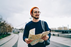 Cheerful caucasian hipster guy in trendy eye wear satisfied with active vacation having trip, smiling male traveler walking with map having city tour excited with urban setting on autumn weekends