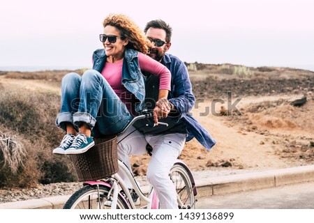 Cheerful caucasian people having fun together in friendship and relationship - adults couple laugh a lot both on a bike enjoying the outdoor leisure activity