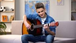Cheerful Caucasian teenager playing guitar, enjoying favorite hobby, leisure