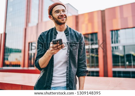 Cheerful caucasian young man dressed in casual wear smiling and looking away while updating app on smartphone standing outdoors.Positive hipster blogger using free 4G internet connection on cellular