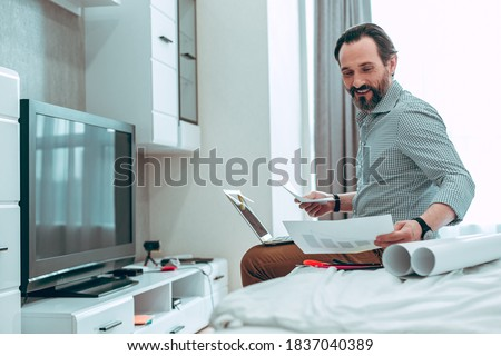 Cheerful Caucasian young man sitting on the bed with a laptop on his laps and smiling while holding sheets of paper stock photo