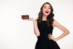 Cheerful charming retro styled young woman holding piece of chocolate birthday cake with candle on the palm over white background