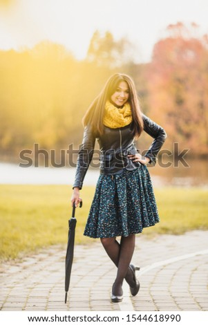 Cheerful cheerful Asian girl with a luxurious hairstyle playfully having fun on the track leaning on an umbrella #1544618990