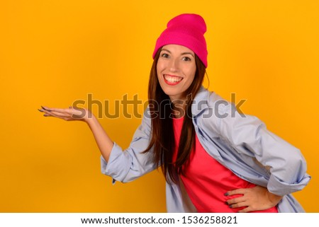 cheerful cheerful woman in a pink hat in a blue shirt holds a free space on her hand on a yellow background #1536258821