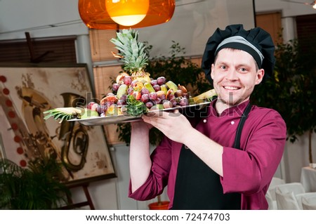 Cheerful chef in kitchen cook uniform holding big plate with fruits set