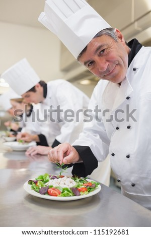 Cheerful Chef's preparing their salads in the kitchen