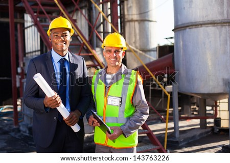 cheerful chemical industry manager and workers at factory