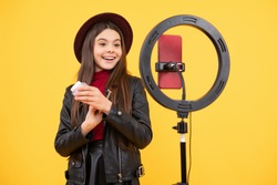 cheerful child do makeup. vlogger with powder brush. making video blog on phone. blogging light lamp. weblog and vlog. makeup tutorial. influencer. happy teen girl use selfie led. kid beauty blogger.