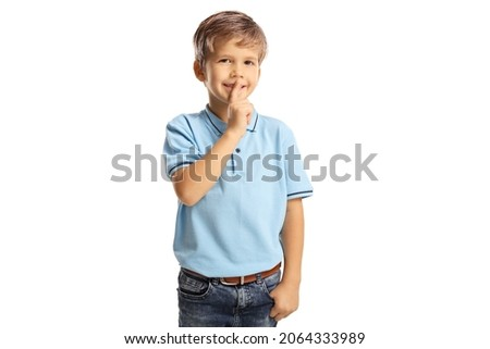 Cheerful child gesutring silence with finger isolated on white background