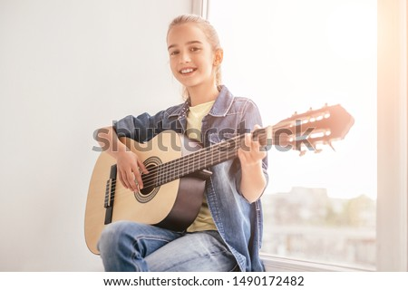 Cheerful child guitarist self-learning playing guitar while sitting next to window in room