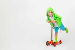 Cheerful child kid in bright green jacket with hood and rubber boots rides scooter on white background with copy space. Studio shot Toddler, boy 4 years old. Childhood and active leisure concept.