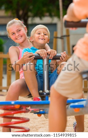 Stock Photo Cheerful children are teetering on the swing on the playground.