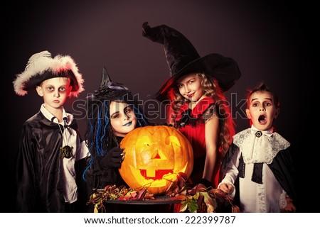 Cheerful children in halloween costumes posing with pumpkin over dark background.