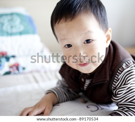 Cheerful chinese baby kid lying in bed at home