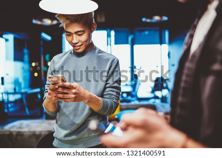 Cheerful Chinese young man dressed in casual wear installing app on smartphone using 4G internet connection standing in modern office. Positive Asian hipster guy blogger chatting online on cellular